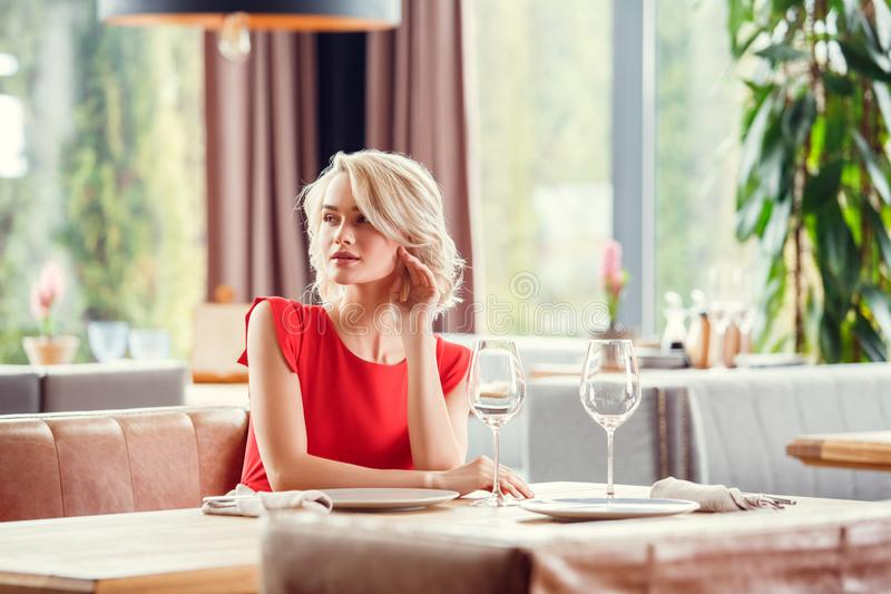 Young woman on date in restaurant sitting looking aside sensual royalty free stock image