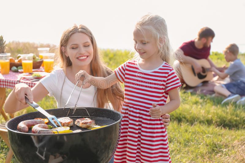 Young woman with daughter cooking meat, sausages and vegetables on barbecue grill while her husband is teaching son to play guitar royalty free stock image