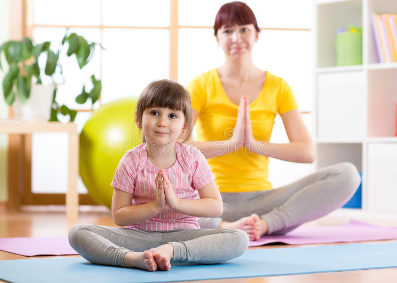 Young woman and daughter doing yoga exercise at home stock photos