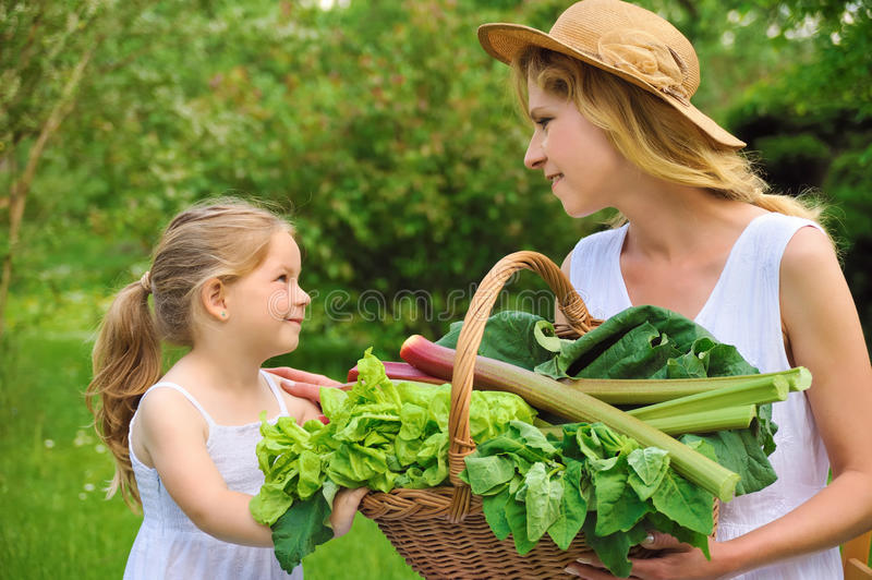 Young woman and daughter with fresh vegetable royalty free stock images