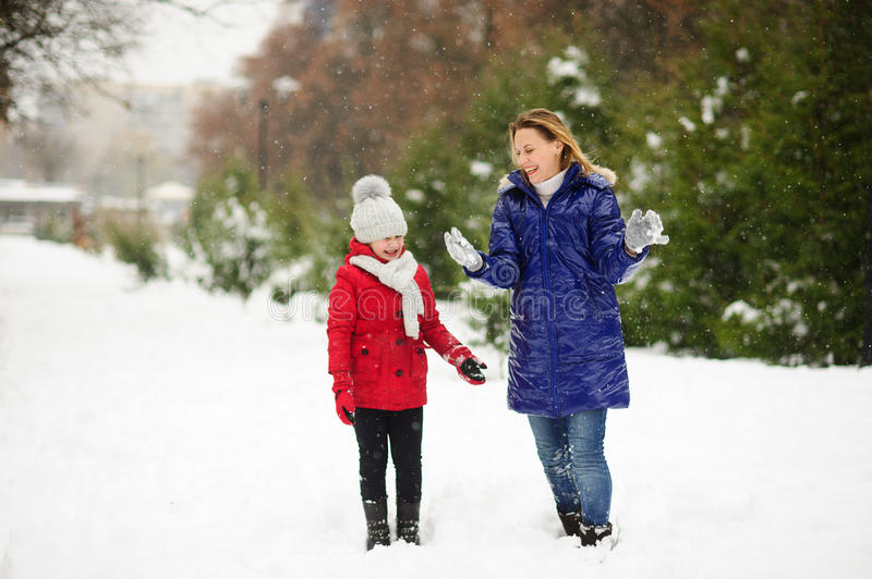 Young woman with the daughter on walk in winter day. royalty free stock photos