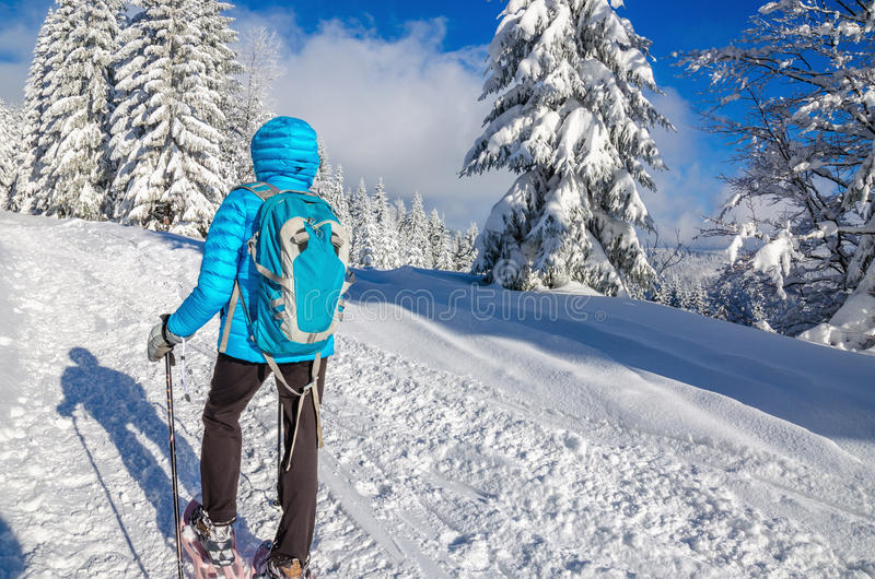 Young woman in dawn jacket hiking with snow shoes. Young woman in down jacket hiking with snow shoes in winter scenery stock image