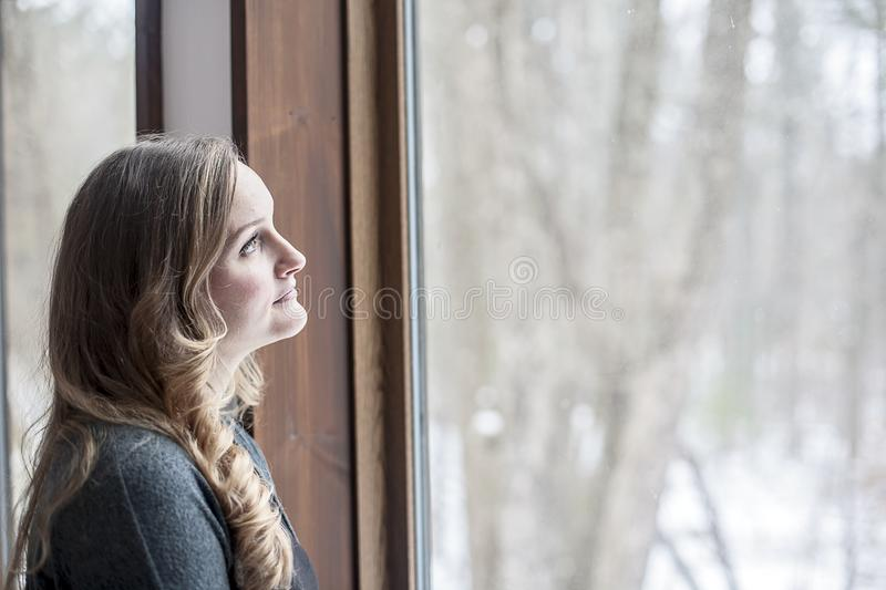 Young woman day dreaming and looking out window stock images