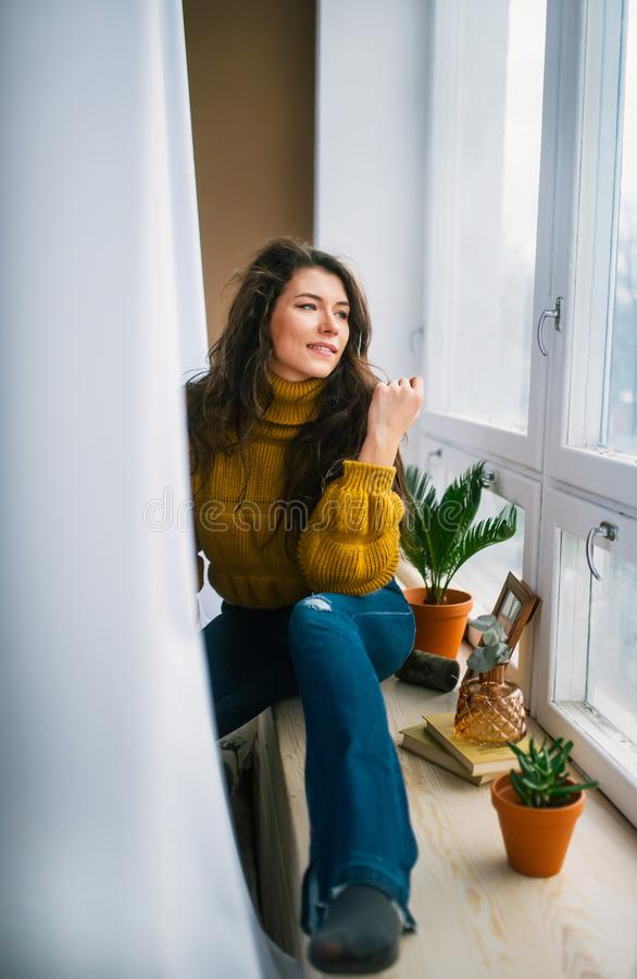 Young woman daydreaming on a beautiful day, sits by a window on sill stock photo