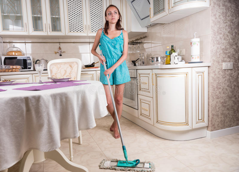 Young Woman Daydreaming and Mopping Kitchen Floor. Full Length of Young Brunette Woman Performing Household Chores by Mopping Floor in Clean Kitchen and Looking royalty free stock photo