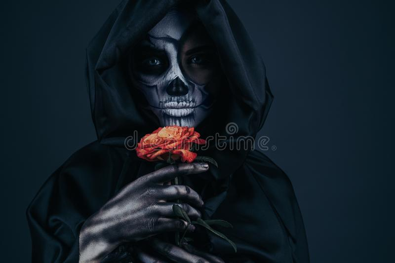 Female death with dried rose. Young woman in death costume holding fragile dried rose and looking at camera while celebrating Halloween against dark gray stock photo