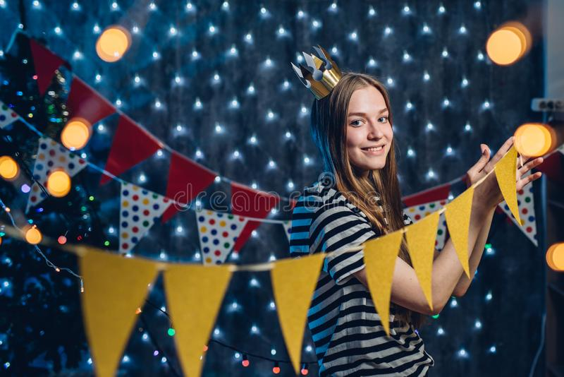 A young woman decorates room Flags, garlands preparing for the celebration Christmas. royalty free stock images