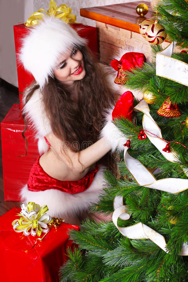 Download Young Woman Decorating Christmas Tree Stock Photo - Image of present, female: 22384180