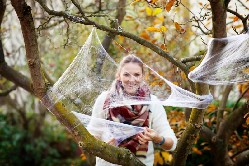 Young woman decorating home garden for halloween with spider web. Family celebrating holiday. Selective focus on web stock photo
