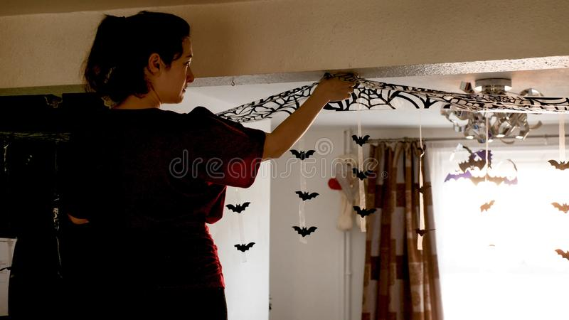 Young woman decorating home for halloween celebration by putting shiny plastic bats and net on ceiling.  stock photos