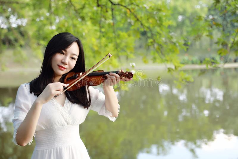 Young woman Dedicated playing violin ,Silhouette of teenage violin player over sunset on river,lake royalty free stock image