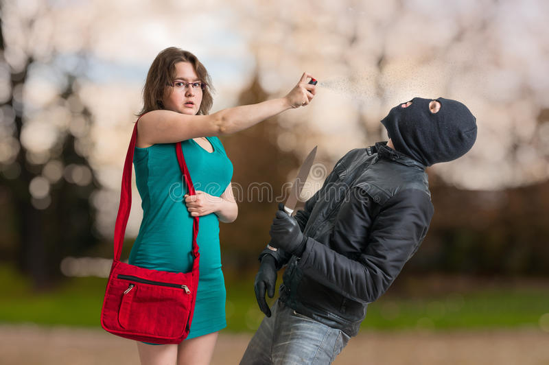 Young woman is defending with pepper spray against armed thief. Young women is defending with pepper spray against armed thief with knife stock photos