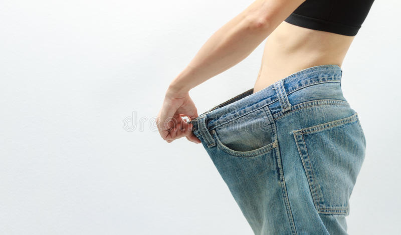 Young woman delighted with her dieting results on white background,A slim woman is showing how much weight she stock photos