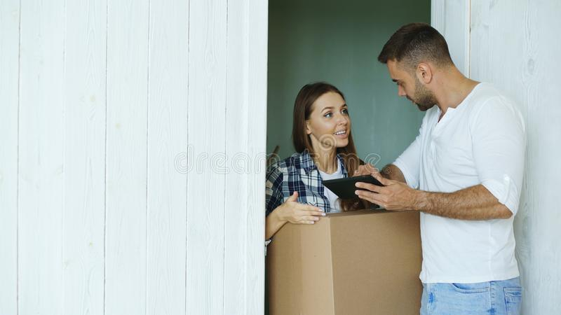 Young woman deliver cardboard box to customer at home. Man write digital signature on tablet computer for receiving royalty free stock images
