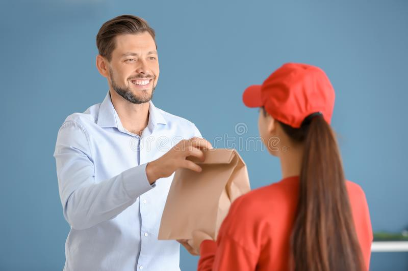 Young woman delivering food to customer indoors. Young women delivering food to customer indoors stock photo