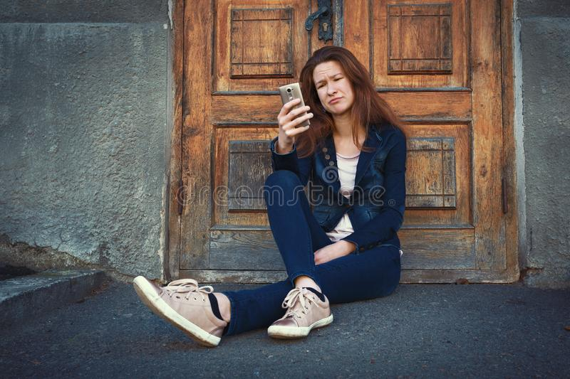 Young woman sitting over old fashioned wooden door and feeling confused royalty free stock photo