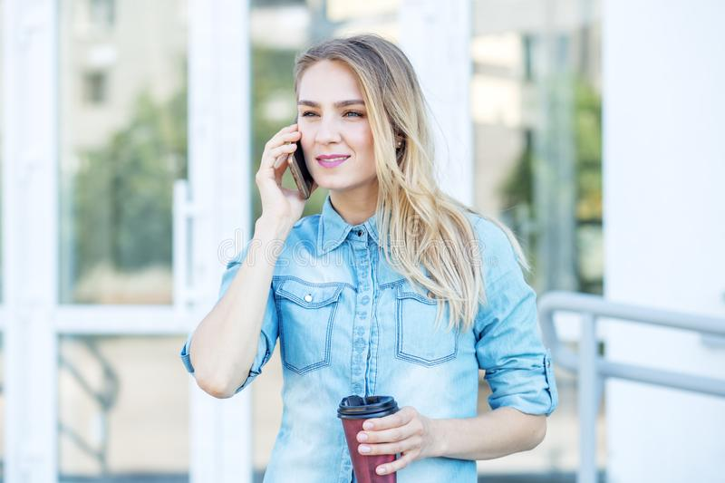 Young woman in denim shirt with smartphone. Concept of life style, urban, work. royalty free stock photography