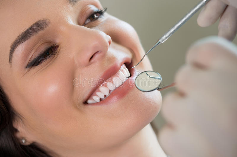 Young woman at the dentist. Closeup of dentist examining young woman's teeth stock photography
