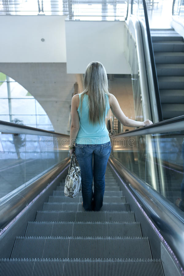 Download Young Woman Descending An Escalator Stock Image - Image of commuters, people: 26051783
