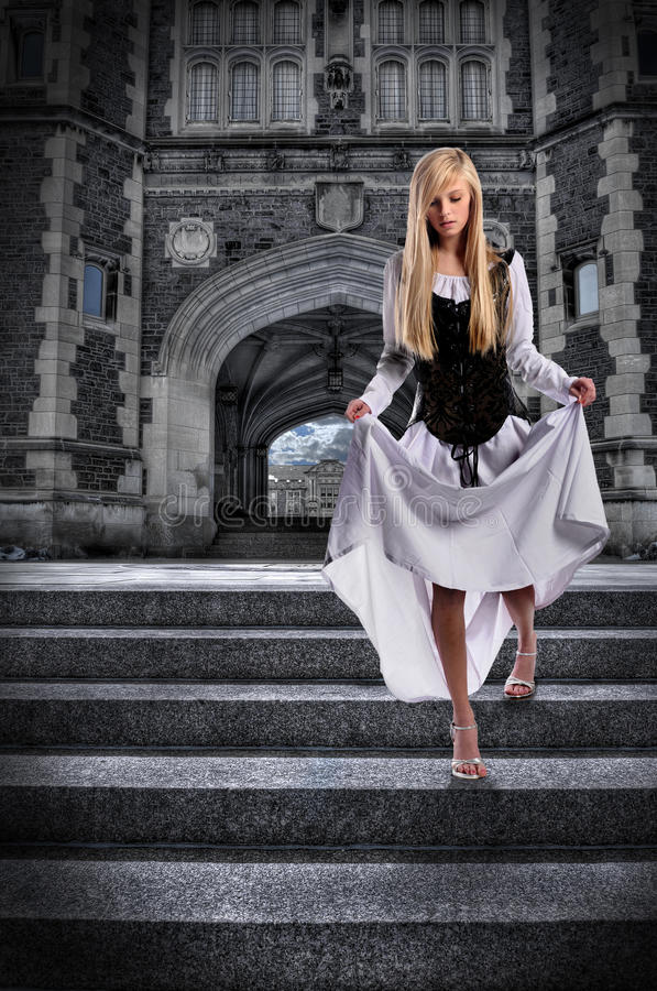 Young Woman Descending Steps of Castle stock image