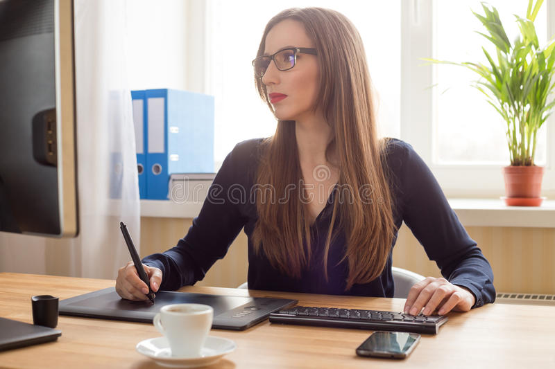 Young woman designer drawing on graphic tablet royalty free stock photography
