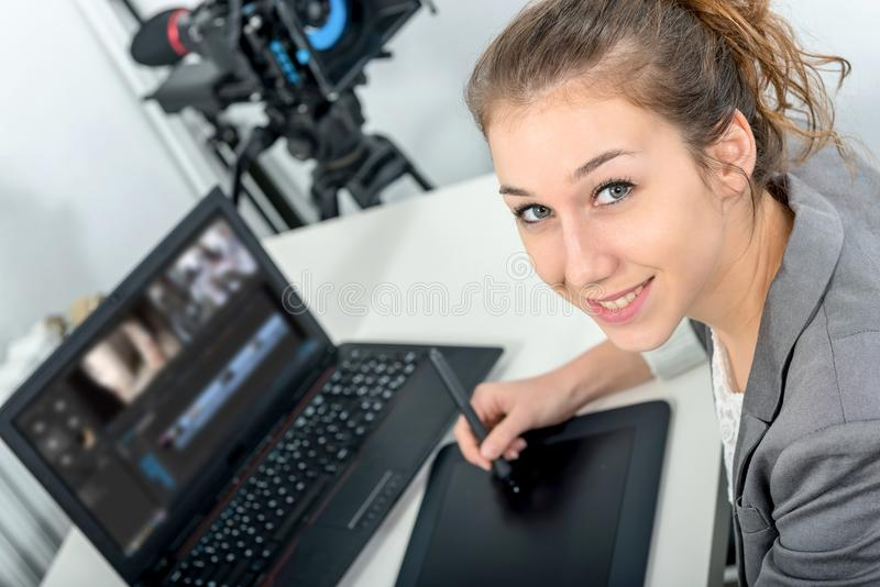 Young woman designer using graphics tablet for video editing stock photos