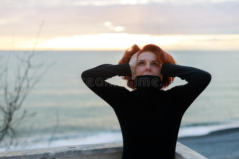 Young woman, in despair, put her hands on her head, directing her gaze towards God. Portrait of a woman with red hair against the royalty free stock image