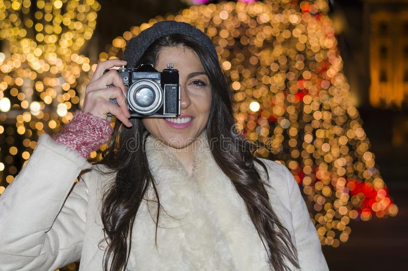 Young woman with digital camera taking photos on a christmas tree background royalty free stock photos