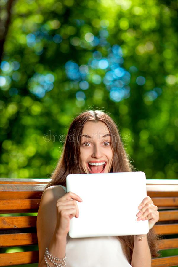 Young woman with digital tablet in the park royalty free stock images