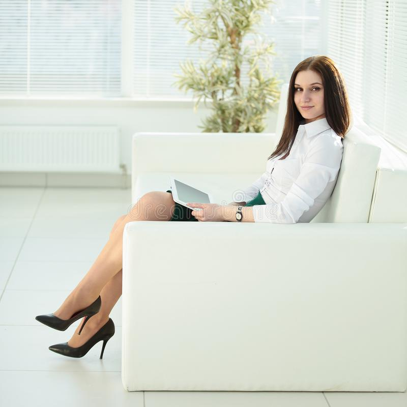 Young woman with digital tablet sitting in the lobby of the office. Photo with place for text royalty free stock photography