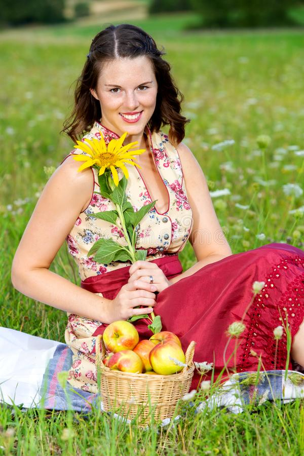 Young woman in dirndl sitting in meadow and holding sunflower. Portrait of young woman in dirndl sitting in meadow and holding sunflower stock image
