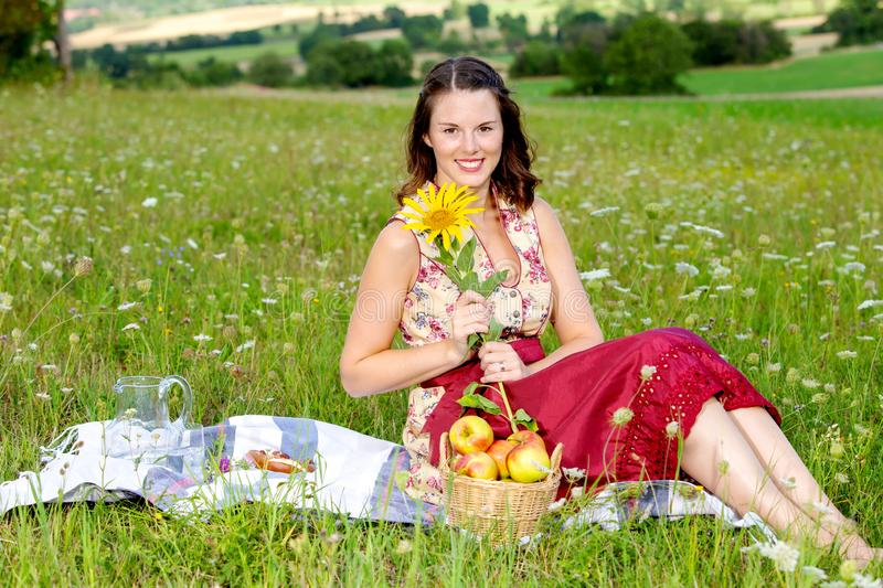 Young woman in dirndl sitting in meadow and holding sunflower. Portrait of young woman in dirndl sitting in meadow and holding sunflower stock photo