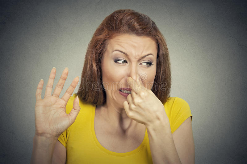 Young woman disgusted by smell looks displeased, something stinks royalty free stock photo