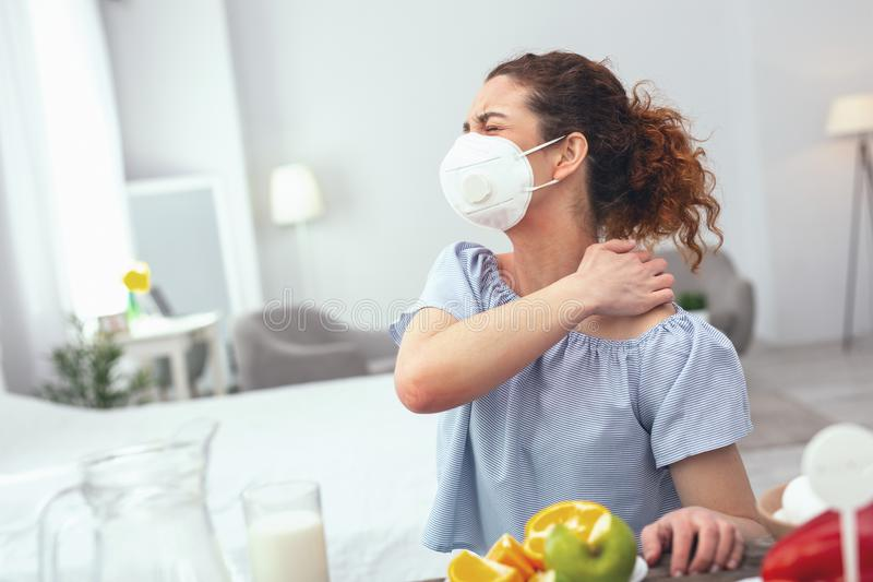 Young woman displaying food allergy symptoms. Food allergy symptoms. Young sore looking woman in a respiratory mask scolding her face in pain while scratching stock image
