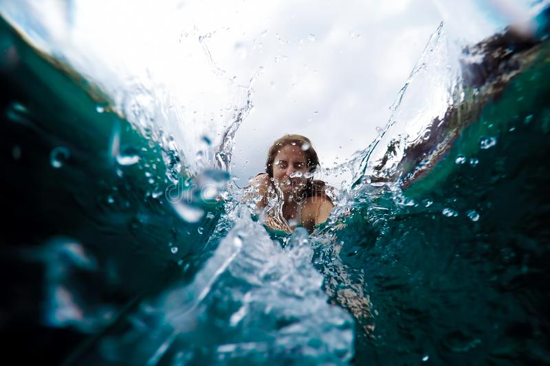Young woman dives into the water. View from under the water, spray. Summer holiday concept, jump to the pool stock photos