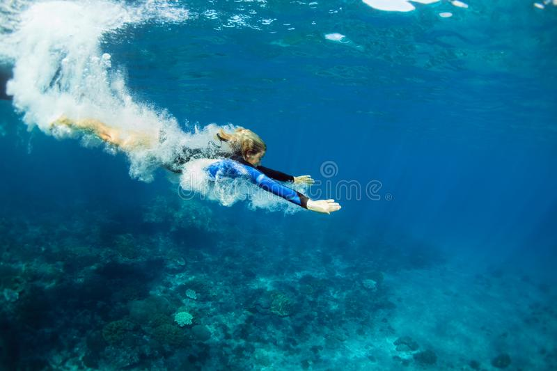 Young woman diving underwater. Happy family - active teenage girl jump and dive underwater in tropical coral reef pool. Travel lifestyle, water sport, snorkeling royalty free stock photography
