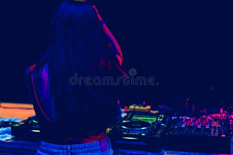 Young woman Dj playing music at night festival. Fun, youth, entertainment and fest concept. royalty free stock photos