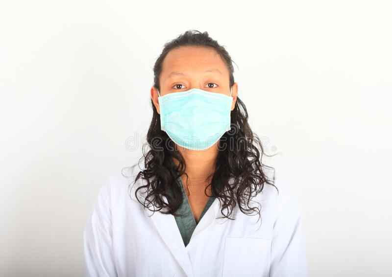 Asian doctor in medical mask. Young woman doctor - Asian girl in white lab coat and medical mask against coronavirus. Virus SARS-CoV-2 and disease COVID-19 stock images