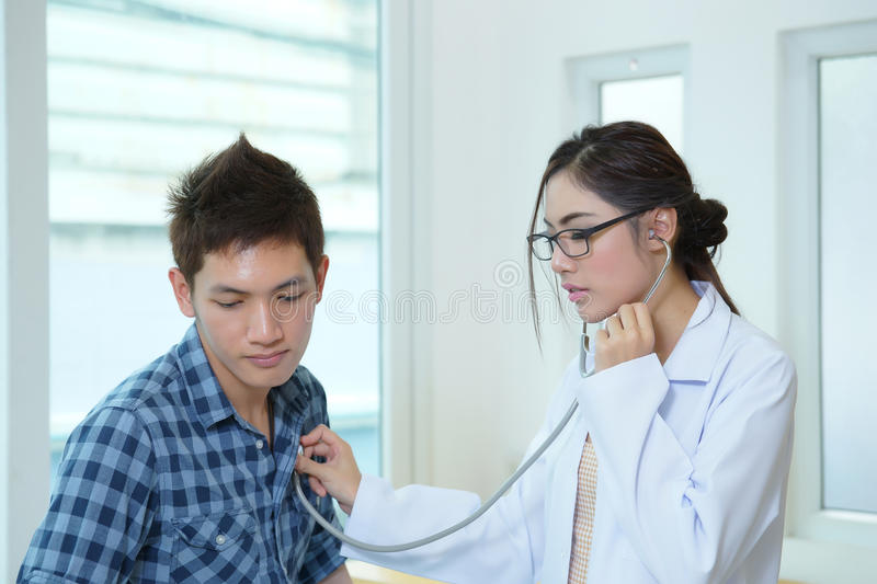 Young woman doctor auscultating male with stethoscope stock photos