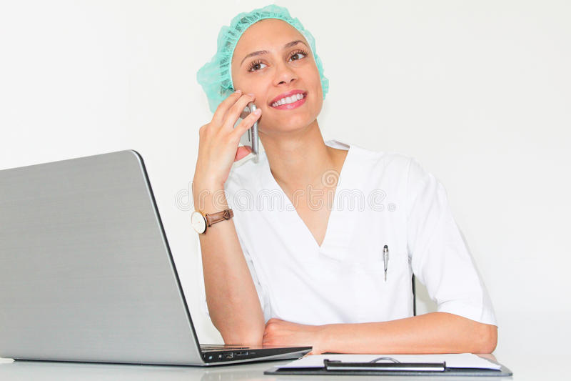 A young woman doctor With a laptop in her office talking on the phone. With a big smile stock image