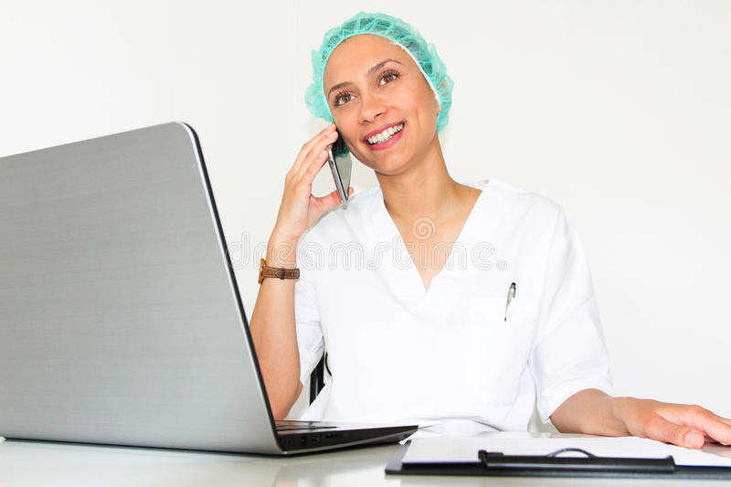 A young woman doctor With a laptop in her office talking on the phone. With a big smile royalty free stock images