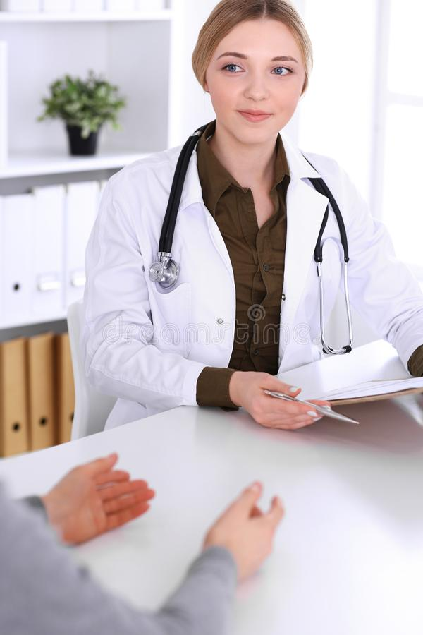 Young woman doctor and patient at medical examination in hospital office. Khaki colored blouse of therapist looks good. Medicine, healthcare and doctor`s stock photography