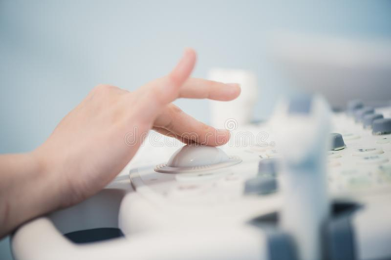 Young woman doctor`s hands close up preparing for an ultrasound device scan. Young woman doctor`s hands close up preparing for an ultrasound device scan royalty free stock photo