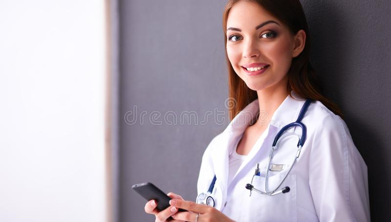Young woman doctor sitting with your phone. Near grey wall stock photography