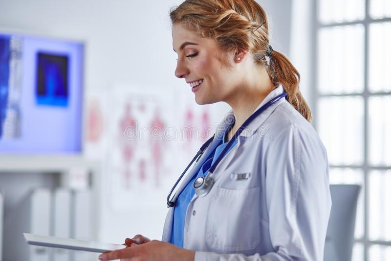 Young woman doctor is standing with board with clipboard smiling in hospital office royalty free stock photos