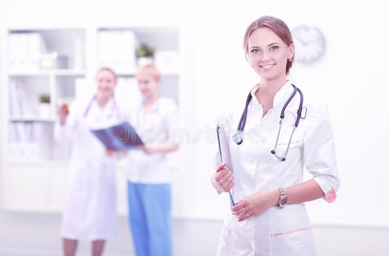 Young woman doctor standing at hospital with medical stethoscope stock photography