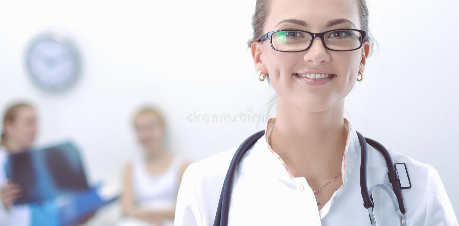 Young woman doctor standing at hospital with medical stethoscope royalty free stock photos
