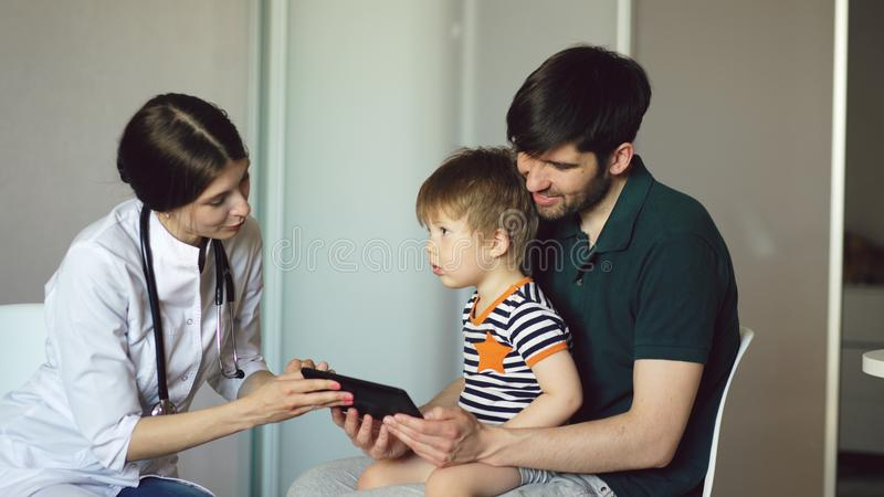 Young woman doctor talking with father of little boy using tablet computer in medical office. Young women doctor talking with father of little boy using tablet royalty free stock photos