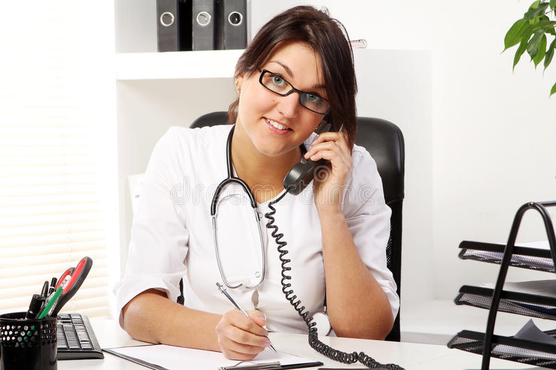 Young woman doctor talking by phone. In her office stock images