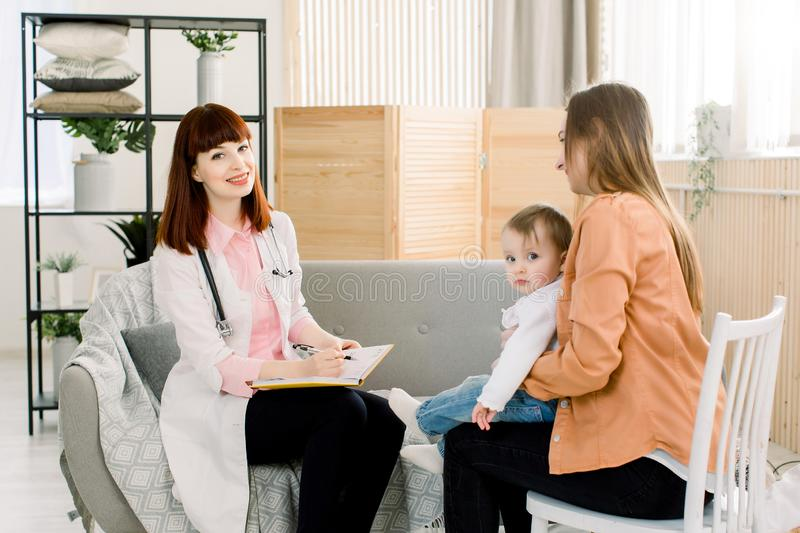 Young woman Doctor in white coat writing something in notebook and mother with baby girl at home. medicine, healthcare royalty free stock photography